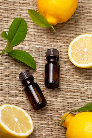 two bottles of lemon essential oil, fresh lemon on a straw background (selective focus) Stock Photo