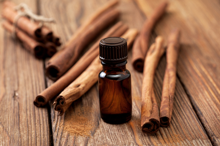 Glass bottle with essential oil of cinnamon, cinnamon sticks on a wooden background Stock Photo