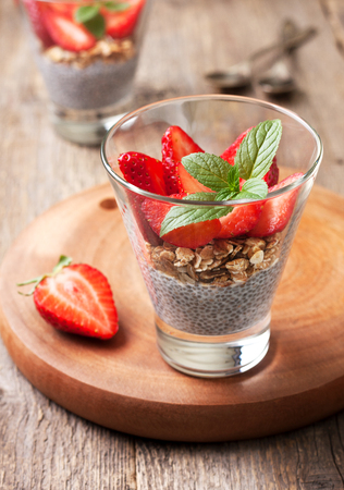 diet healthy breakfast. chia pudding, strawberries and muesli in a glass , fresh strawberry on  old wooden background