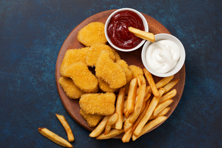 Chicken nuggets and french fries, sauces of ketchup and mayonnaise on a blue background. view from above