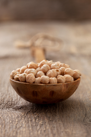 Chickpeas in a wooden spoon on the old wooden background close-up