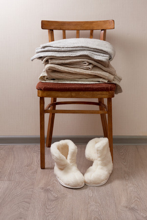 stack of warm clothes on the chair, Pair of warm winter sheepskin slippers Stock Photo