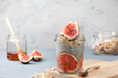 background texture: healthy breakfast. chia pudding with figs, muesli in a glass jar on a gray concrete background