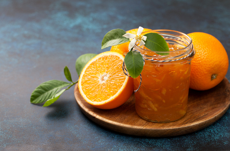 orange jam in a glass jar, fresh oranges on a wooden plate on a blue background 스톡 콘텐츠