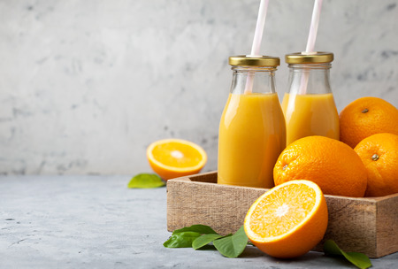 cold cut: orange juice in glass bottles, fresh oranges in a wooden tray (box) on a gray concrete background