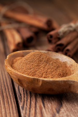 Ground cinnamon in a wooden spoon, cinnamon sticks on old wooden background