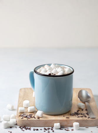hot chocolate with marshmallow, chocolate sprinkling in a blue mug on a light background close-up Stockfoto