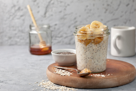 healthy diet breakfast. overnight oatmeal with chia seeds, bananas, peanut butter, honey in a glass jar on a gray concrete background 版權商用圖片