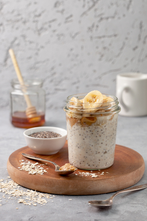 healthy diet breakfast. overnight oatmeal with chia seeds, bananas, peanut butter, honey in a glass jar on a gray concrete background Standard-Bild