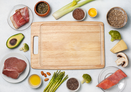 Ingredients for ketogenic diet: meat, bacon, fish, broccoli, asparagus, avocado, mushrooms, cheese, sunflower seeds, chia seeds, pumpkin seeds, flax seeds. view from above. copy space Stock Photo