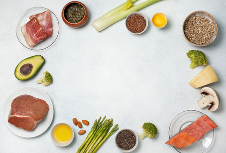 Ingredients for ketogenic diet: meat, bacon, fish, broccoli, asparagus, avocado, mushrooms, cheese, sunflower seeds, chia seeds, pumpkin seeds, flax seeds. view from above. copy space Standard-Bild