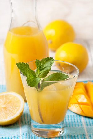 mango lemonade with a mint branch in a glass on a blue napkin, fresh mango and lemons on a white wooden background