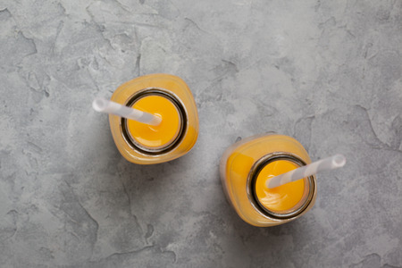 orange juice in a glass bottle on a gray background. view from above