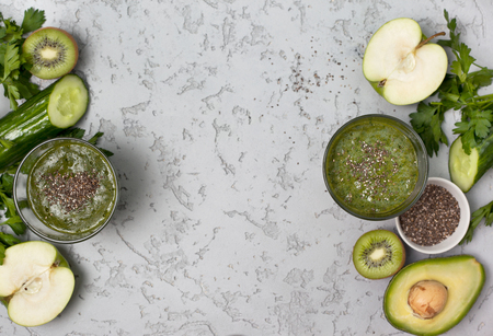 green smoothies in a glass, fresh vegetables, fruits, herbs on a gray concrete background. view from above