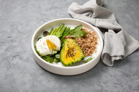 healthy diet breakfast. quinoa, avocado, asparagus, poached egg  in a white ceramic plate on a gray stone background