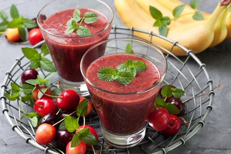 cherry smoothies in a glass on a gray concrete background Stock Photo
