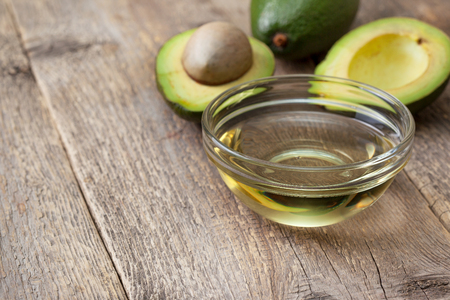 oil in a glass bowl, the two halves of avocado on the old wooden background