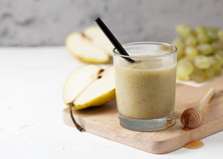 Smoothies of pears and grapes in a glass on a white background concrete Stock Photo
