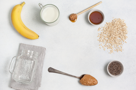 ingredients for night oatmeal with bananas, chia seeds on a light concrete background. view from above. copy space Stock Photo