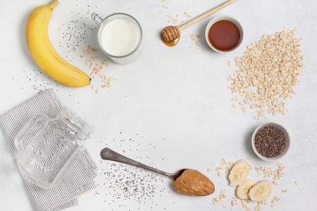 Ingredients for night oatmeal with bananas, chia seeds on a light concrete background. view from above.