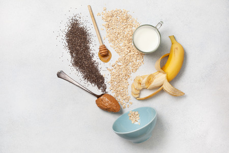ingredients for overnight oatmeal with bananas, chia seeds on a light concrete background. view from above.