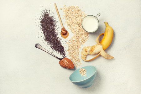 ingredients for overnight oatmeal with bananas, chia seeds on a light concrete background. view from above. toning
