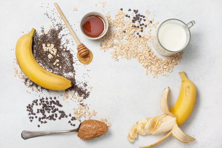 ingredients for a overnight oatmeal with bananas, chocolate drops on a light concrete background. view from above. copy space Stock Photo