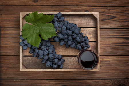 wooden box with grapes and a glass of wine on the old wooden background. view from above