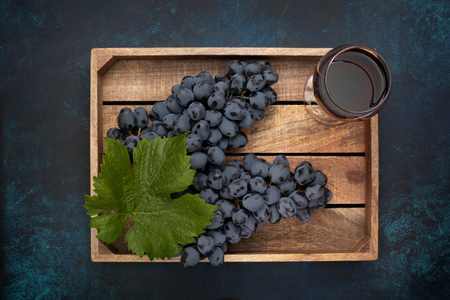 wooden box with grapes and a glass of wine on the blue background. view from above