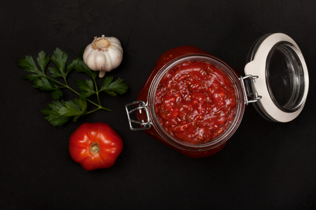 tomato sauce in a glass jar, a branch of parsley, fresh tomatoes and garlic on a black background. view from above