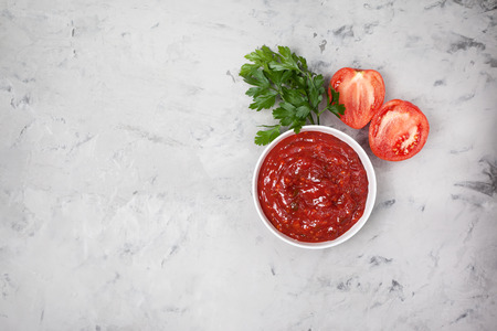 tomato sauce in a white bowl, fresh tomatoes and parsley on a gray concrete background. view from above Stock Photo