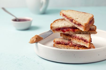 Toast with peanut butter and jam in a white ceramic plate on a blue concrete background Stock Photo