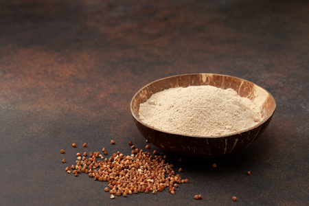 buckwheat flour in a bowl, buckwheat on the concrete background. copy space
