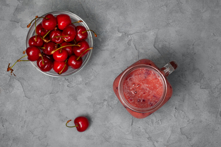 cherry smoothie in Mason jar on a gray concrete background. view from above