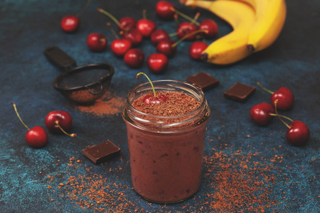 cherry chocolate smoothie (black forest) in a jar on a dark blue background. toning Foto de archivo