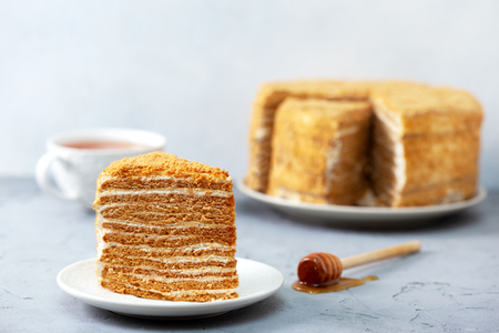 Piece of homemade honey cake on a white plate on a gray concrete