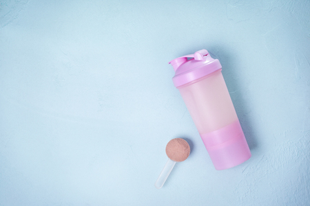 Shaker with protein drink on a blue