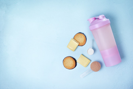 Shake with protein drink, protein powder, protein bars and protein cookies on a blue 스톡 콘텐츠