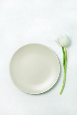 Empty plate and tulip on a light Archivio Fotografico