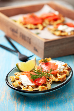 Potato waffles with salmon, cream cheese on a blue wooden Banque d'images