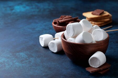 Marshmallows, chocolate and cookies for making smore on blue