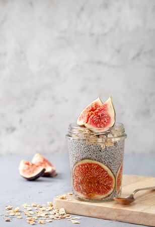 Healthy breakfast chia pudding with figs in a glass jar on a gray 写真素材