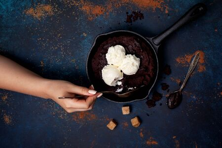 Brownie with chocolate cream and vanilla ice cream in a pan over blue