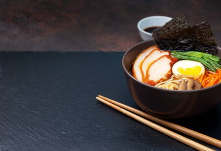 asian ramen soup with chicken, egg, carrots, green onions on a dark background.