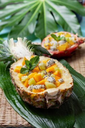 tropical fruit salad in half pineapple from mango, kiwi, dragon fruit. healthy eating.
