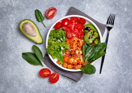 healthy vegan bowl. sweet potatoes, broccoli, avocados, tomatoes, spinach in a white bowl on a gray background. view from above