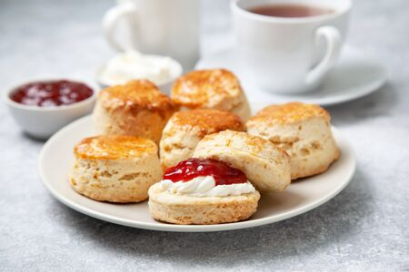 scones on a white plate, a jar of strawberry jam and a cup of tea on a gray background Foto de archivo