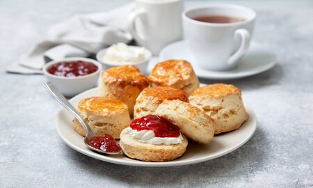 scones on a white plate, a jar of strawberry jam and a cup of tea on a gray background
