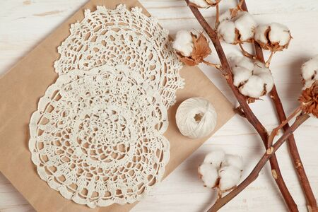 Hobby concept. handmade crocheted white napkins and cotton branches on a wooden background. top view.  版權商用圖片