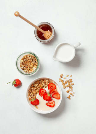 the concept of a healthy breakfast. breakfast with granola, greek yogurt and strawberries in a white bowl .. on a white background. view from above